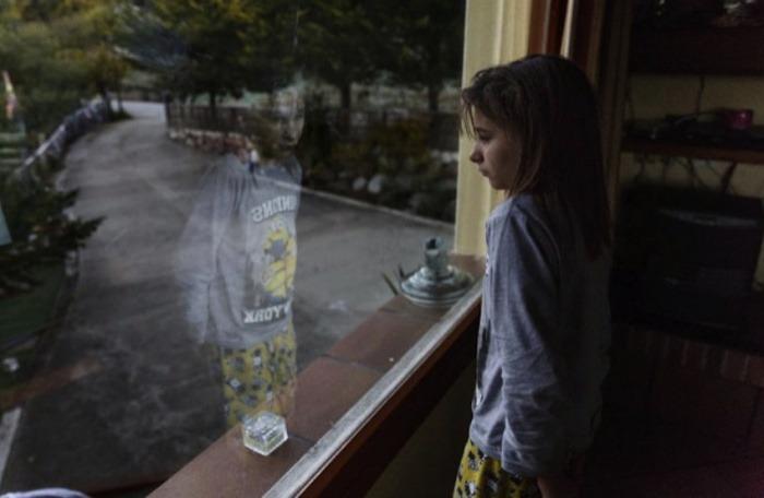 Nadia, mirando por el ventanal de su casa | Fotografía: Carlos García Pozo | Imagen agregada de El Mundo.