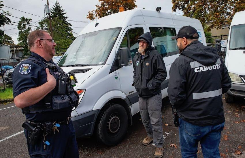 Un oficial de policía hablando con el coordinador de la Clínica White Bird y un trabajador de crisis de emergencia de Cahoots. Foto: Chris Pietsch / The Register-Guard