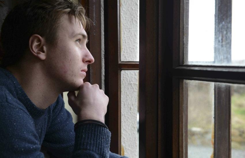 Un joven que sufre de depresión mira por una ventana pensando en el día que tiene por delante. Fotografía: Newscast Online.