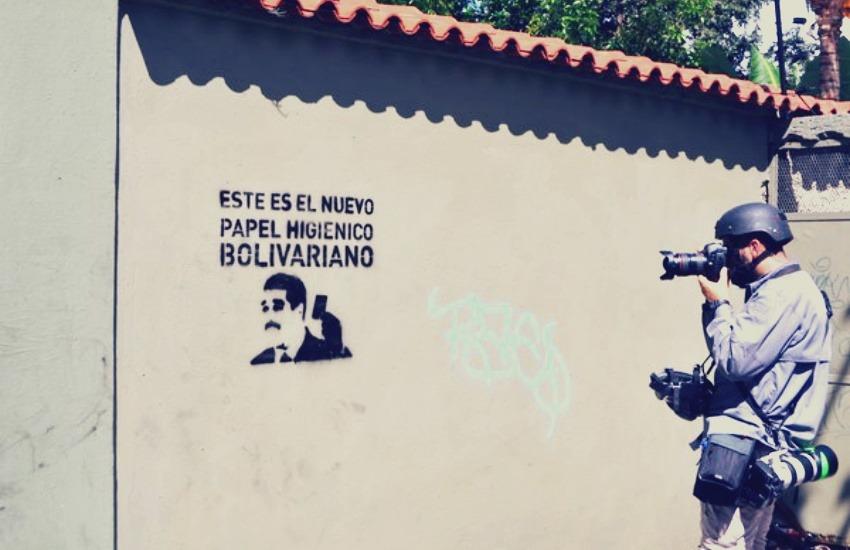 Es habitual ver periodistas usando cascos y máscaras antigas en Venezuela. Fotografía: Marvin Del Cid.